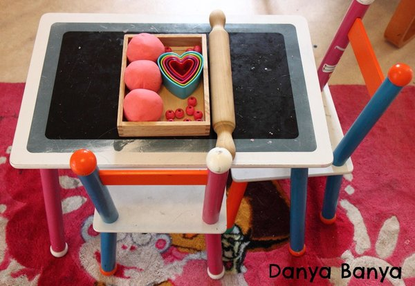 An invitation to play with play dough heart cookie cutters and beads