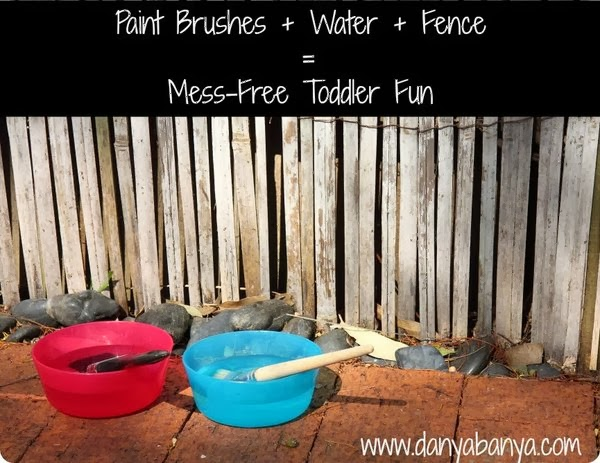 Paint brushes + water + fence = mess-free toddler fun