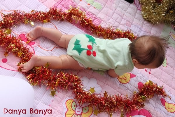 Baby wearing onesie with Christmas holly appliqued on bottom