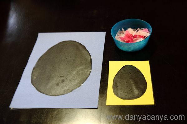Invitation to play - cut out easter eggs with contact paper and a bowl of ripped up tissue paper