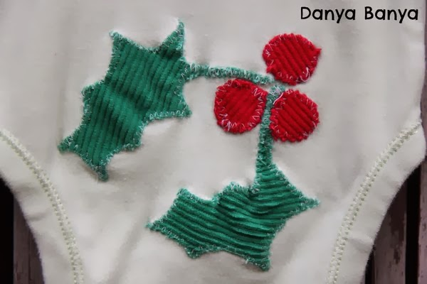Christmas holly appliquéd on the bottom of a baby onesie