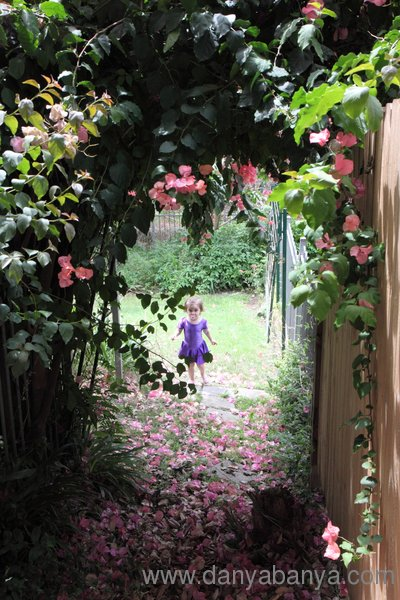 Girl playing under a bougainvillea