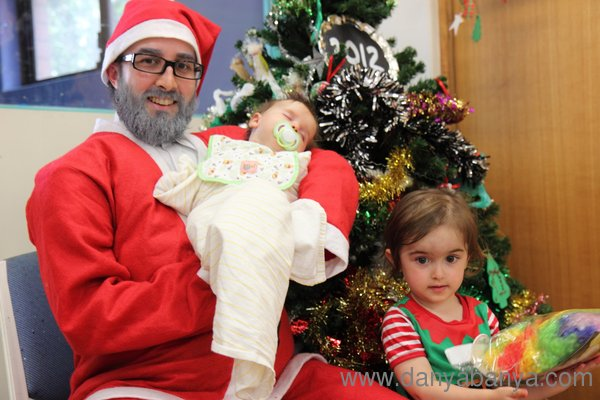 Mr Banya dressed as Santa, holding baby Bee with JJ standing